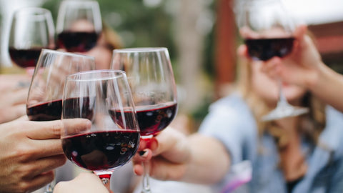 Multiple people with red wine