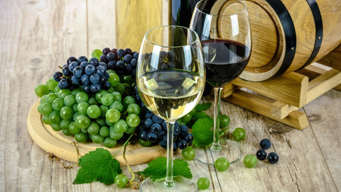 Wine glasses in front of grapes.
