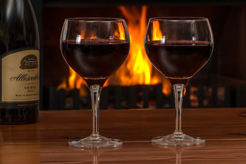 A bottle and two glasses of wine by a fire.