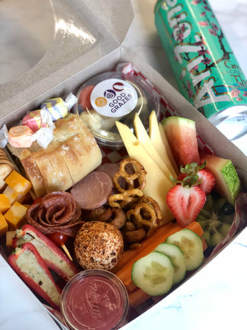 grazing box with watermelon, veggies, summer sausage, stuffed peppers, candy, and more