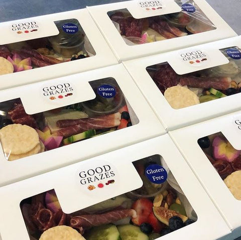 six individual charcuterie grazing boxes with meat, cheese, bread, fruits, vegetables, dips, crackers, with a gluten-free sticker