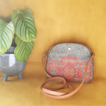 grey bleu with red floral pattern, traditional mediterranean medium crossbody handbag with light brown shoulders strap. vegan leather bag made out of cork presented on a turmeric background and a tropical plant next to it.