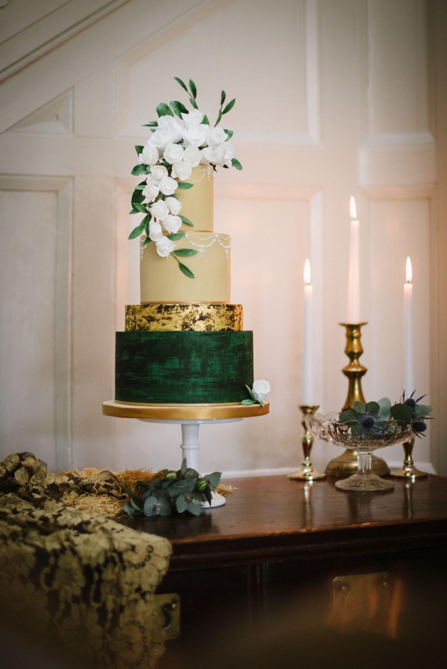 Elegant four tier wedding cake, gold leaf, blush and green with flower cascade topper