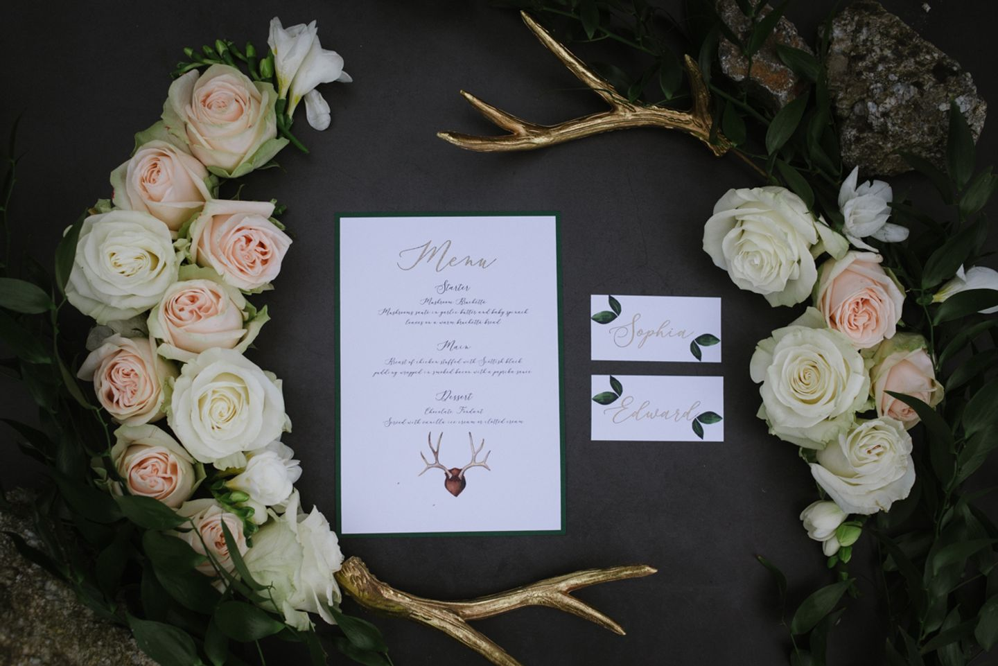 Country House wedding flat lay - gold stag horns and roses adorn modern calligraphy menu and  place cards