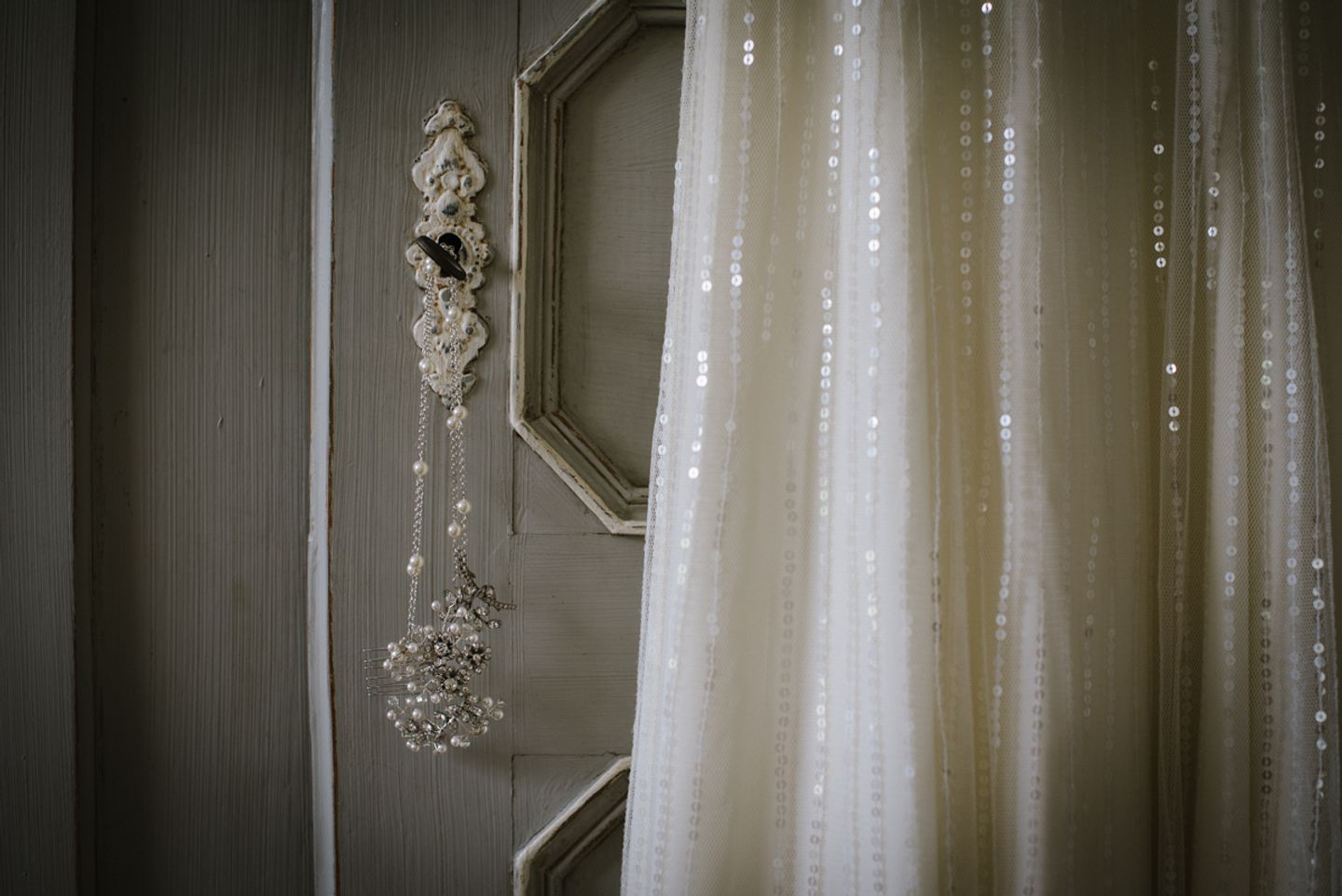 Art Deco bridal accessory hangs from ornate key next to details of subtle sequin wedding dress