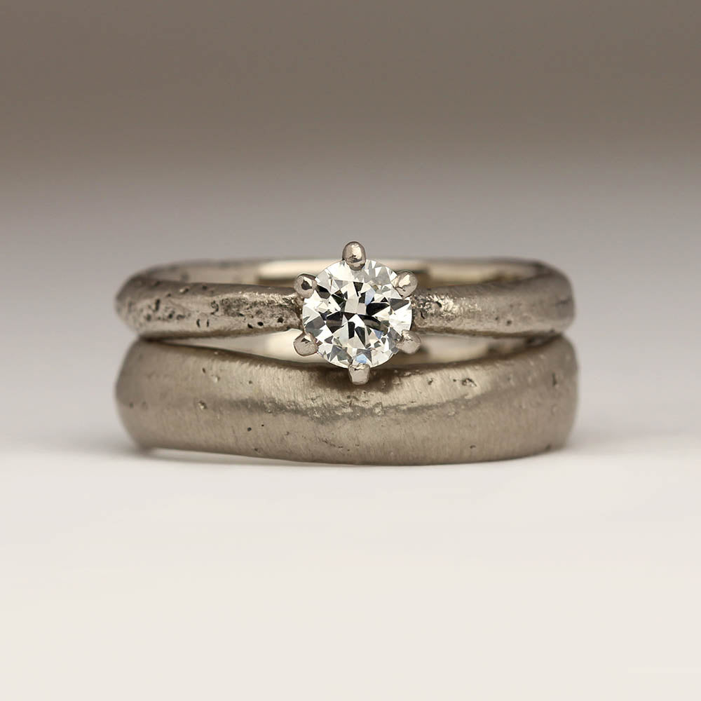 Chunky wedding ring next to engagement ring