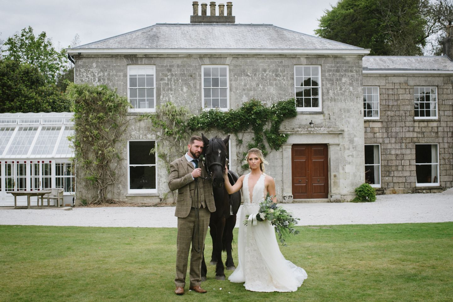 Bride and groom pose with horse in front of Cornish country house