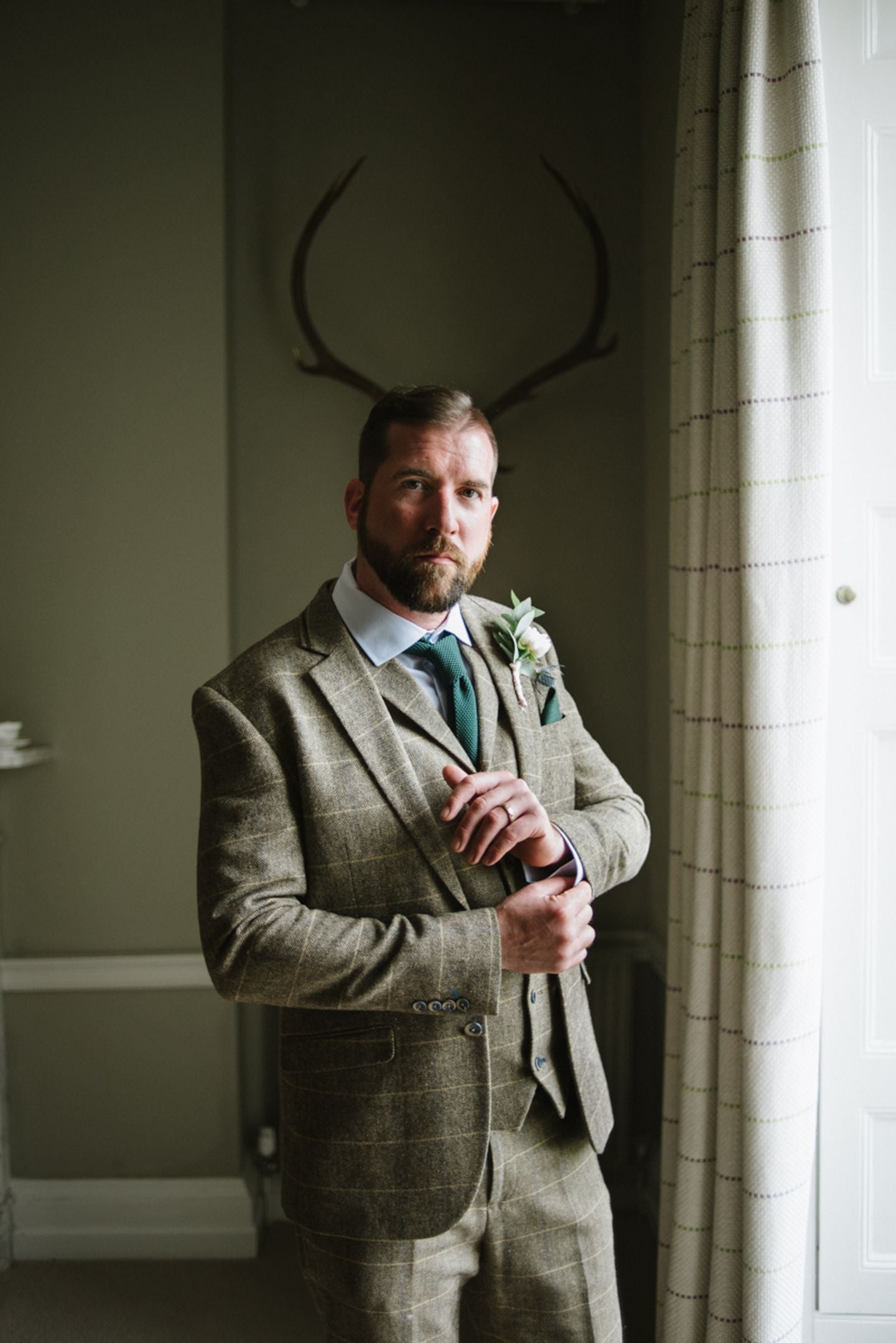 Groom portrait with stag horns, country house wedding