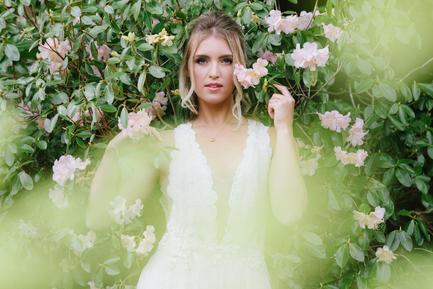 Bride surrounded by pink blossoms in deep plunge lace wedding dress