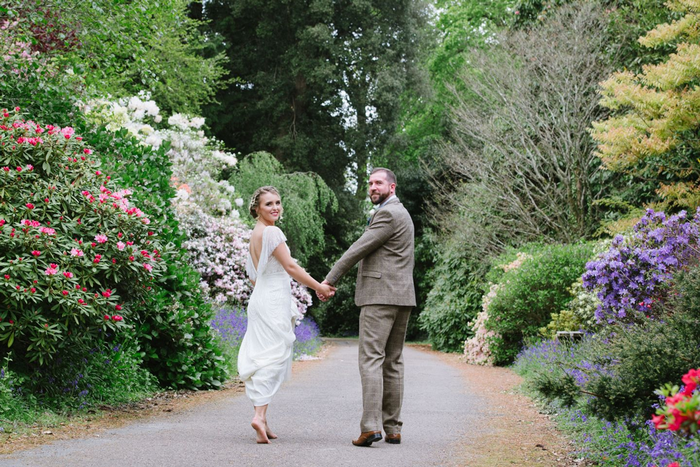 Bride and groom look back towards camera walking through Cornish country house gardens