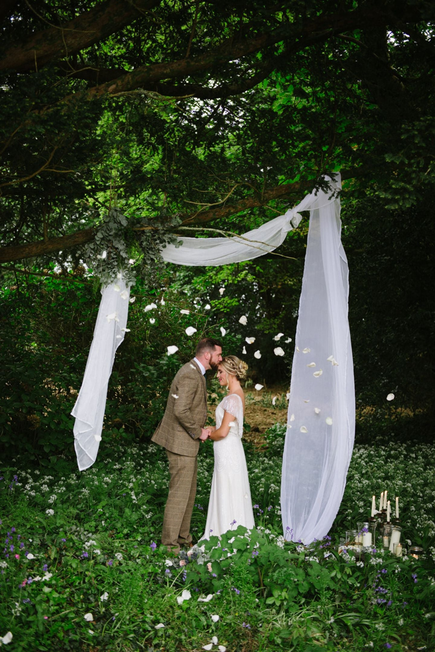 Simple woodland wedding ceremony styling, bride and groom stand below minimal white drapes under trees, he kisses her head, candles are on the floor and rose petals float by