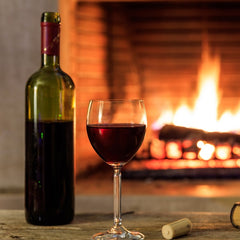 Bottle of red in front of fire