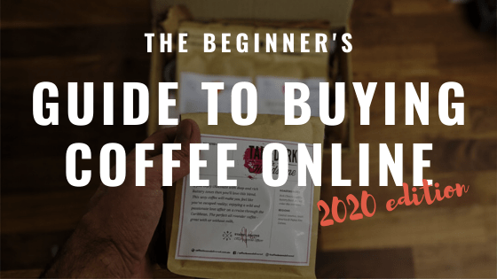 the beginner's guide to buying coffee online 2020 edition text overlay on a male hand holding coffee bag