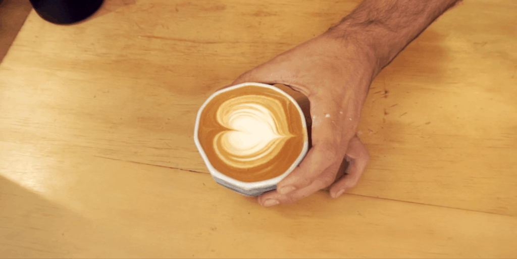love heart latte art shot of cup from above with hand holding it