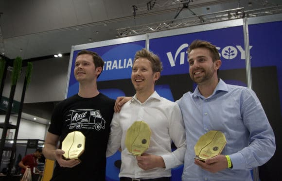 Three males the standing shoulder to shoulder winners of the AUstralian Barista Championships at Melbourne International Coffee Expo 2019