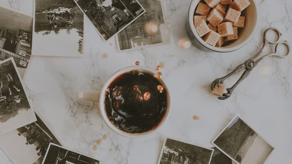 flat lay coffee on a table with sugar lumps in a bowl next to it.Black and white Photographs on the table spread out.