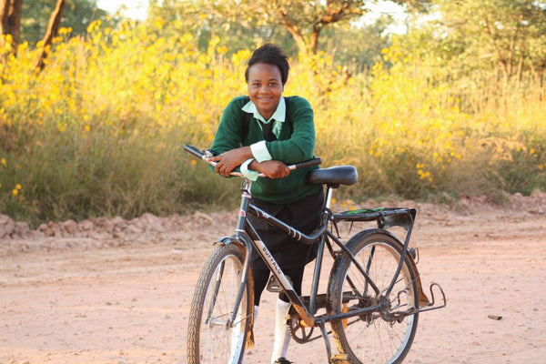 a girl uses her buffolo bike from world bicycle relief to get to school