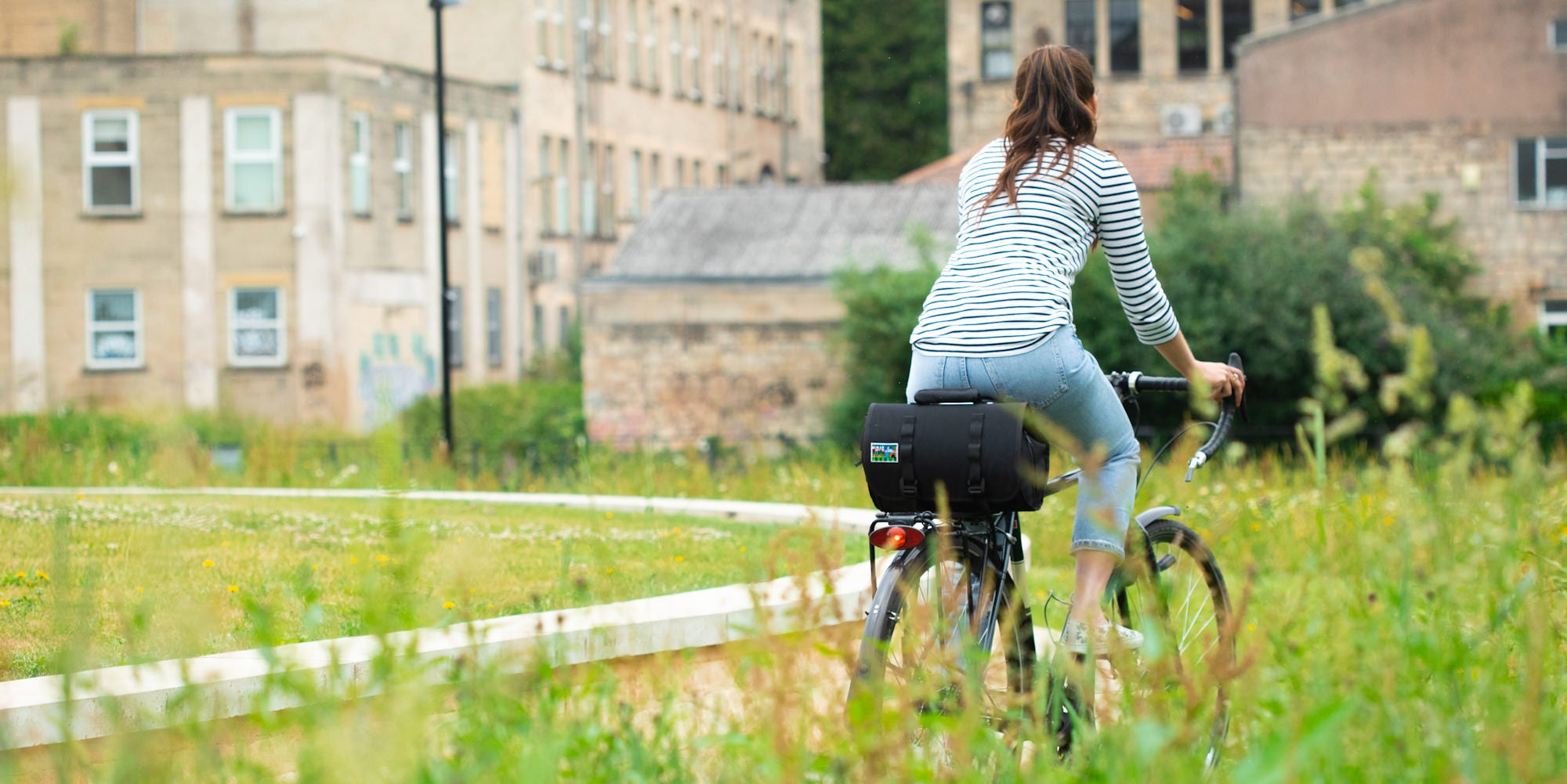 woman cycling to work through a park, commuting to work puts you in a good mood