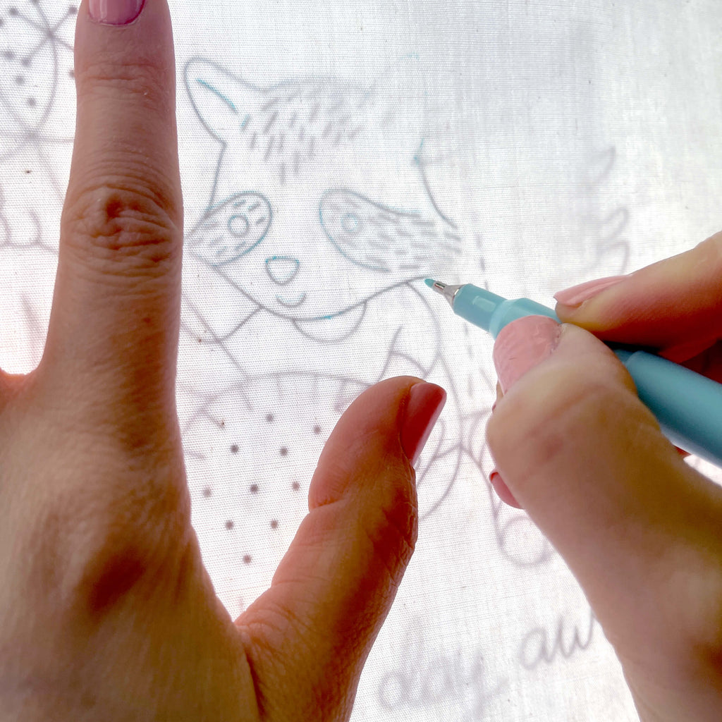tracing the Stitching Raccoon Sampler with a water soluble marker