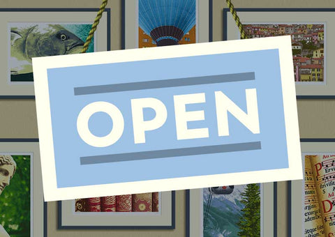 'Open' sign in front of wall of prints