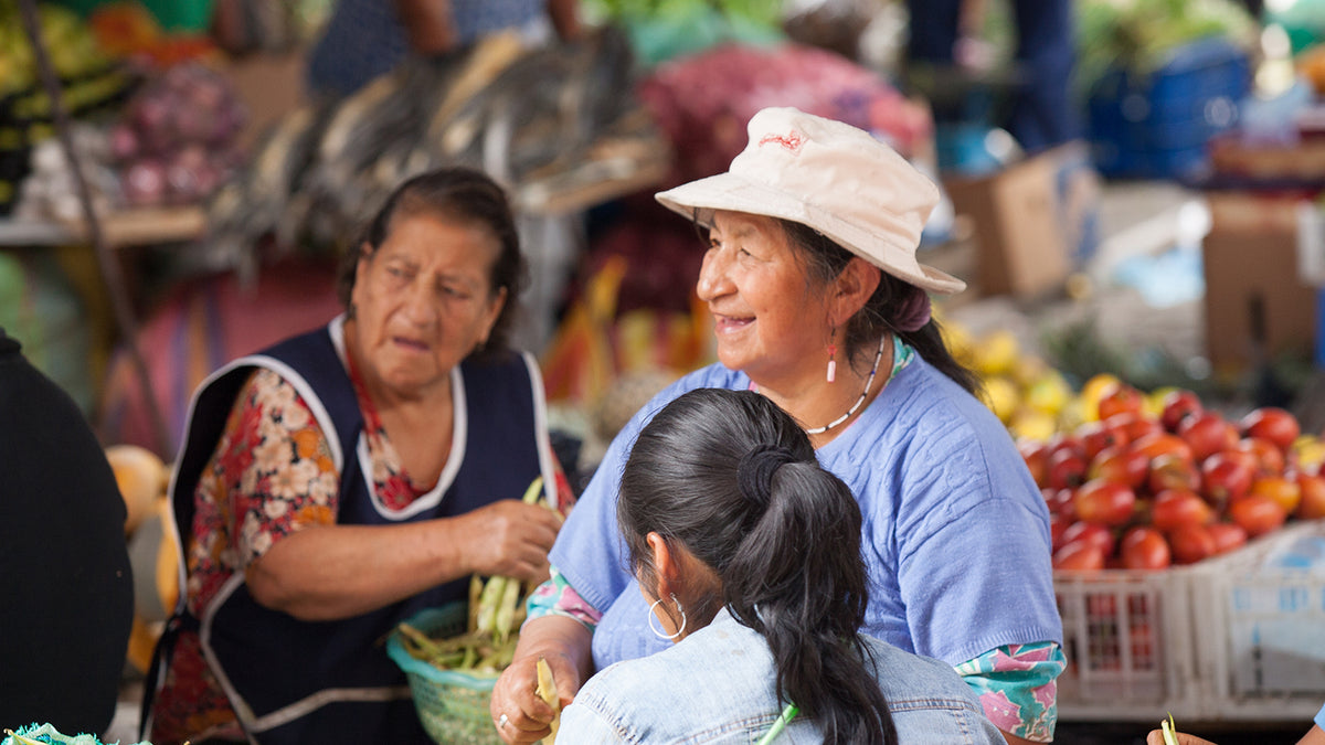 Image of an ecuadorian woman wearing a blue t-shirt and a white sunhat. She is smiling and is sat with other women in a market.