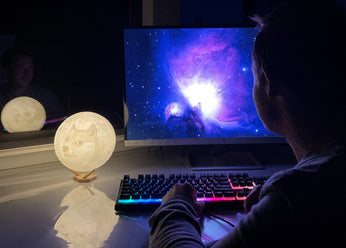 Doge moon lamp with shiba inu meme white next to computer and man