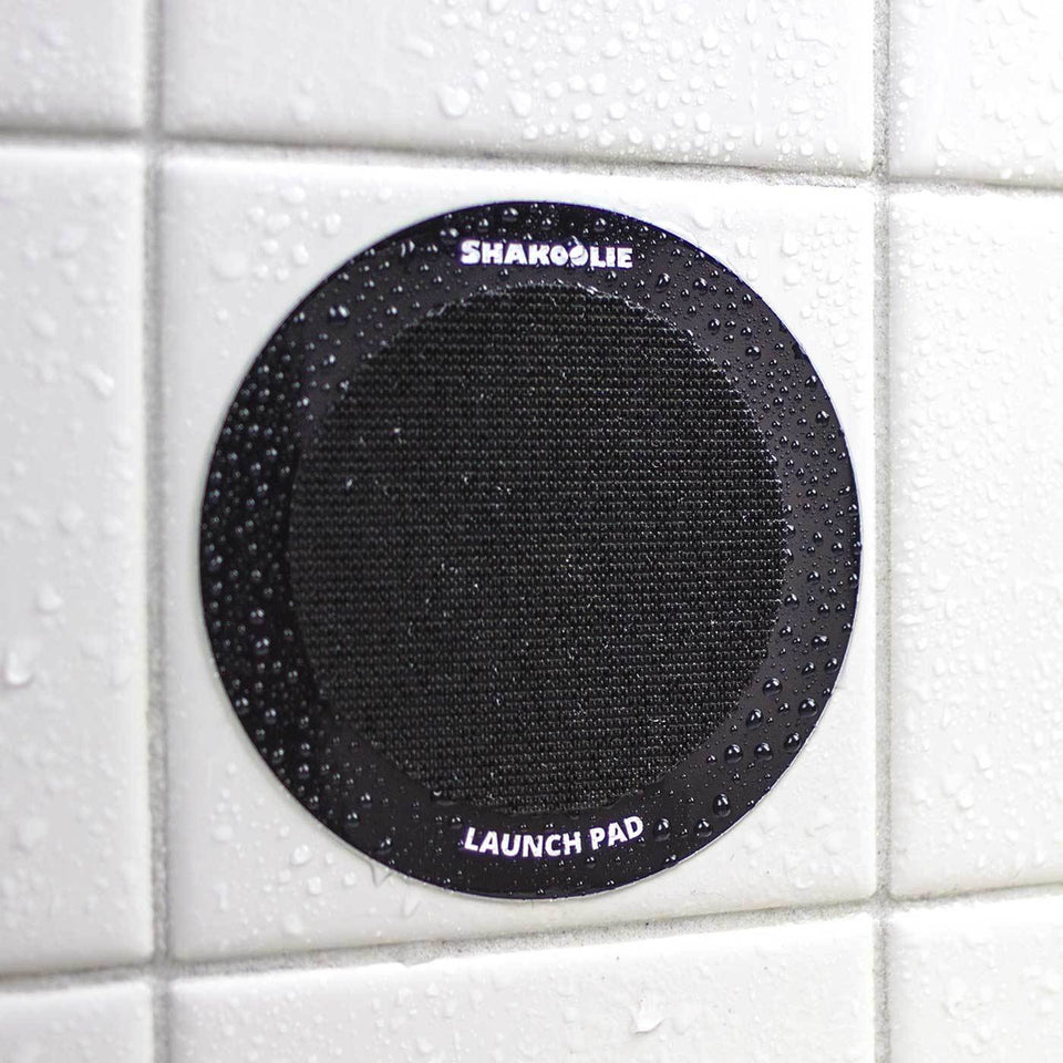 The Launch Pad is a thick vinyl sticker with industrial velcro that holds the foam can beverage holder on your shower wall.