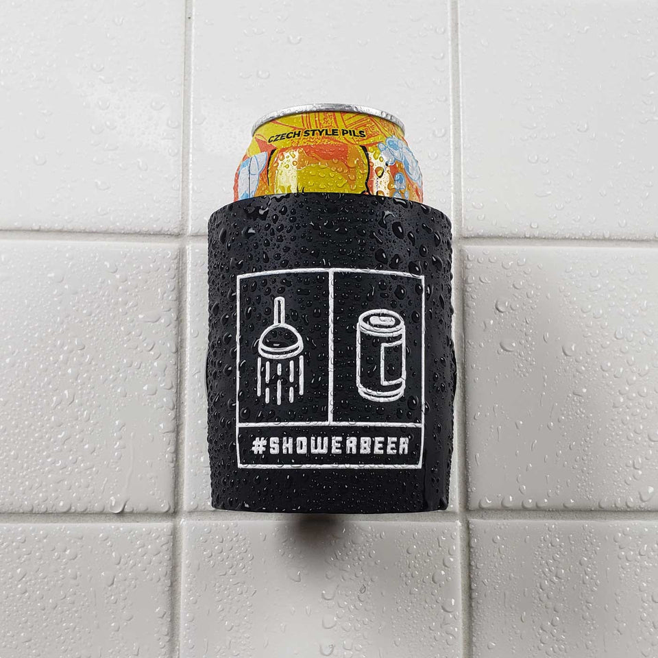 "Foam can beverage holder that sticks to shower wall via industrial velcro. This design is white ink printed on a black can holder with the words ""#SHOWERBEER"" written across the bottom and the artwork depicting a shower head and a canned beer beverage. This is an action shot of the product in a shower."