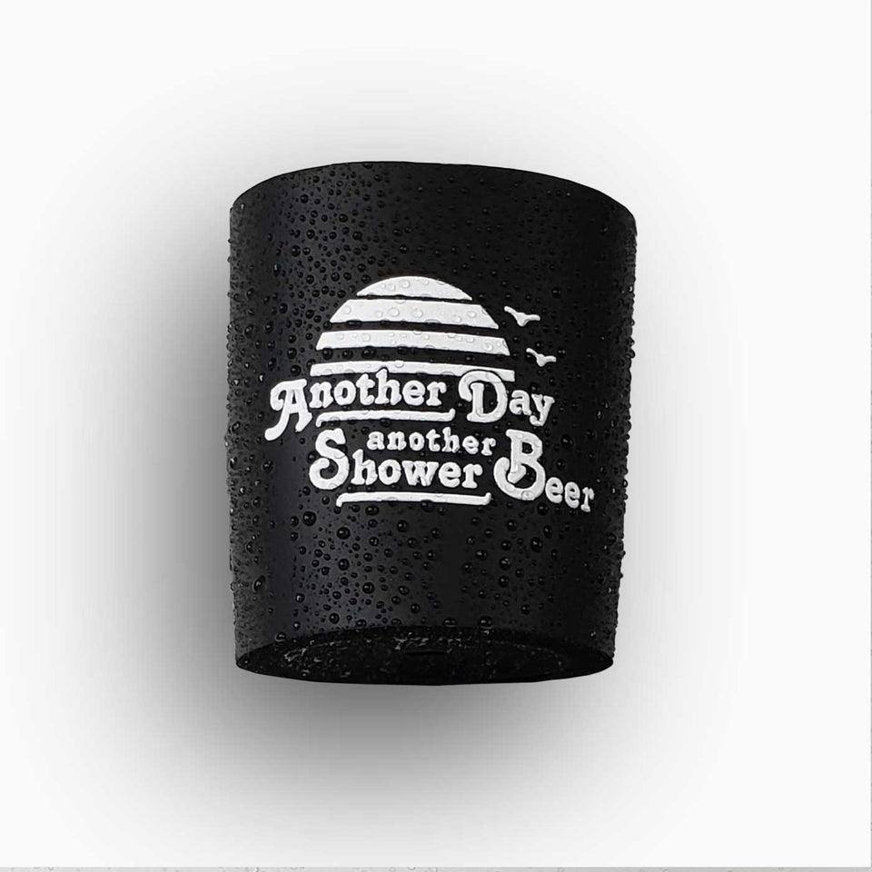 "Foam can beverage holder that sticks to shower wall via industrial velcro. This design is white ink printed on a black can holder with the words ""Another Day Another Shower Beer"" written and artwork depicting a California sunset and two seagulls flying."