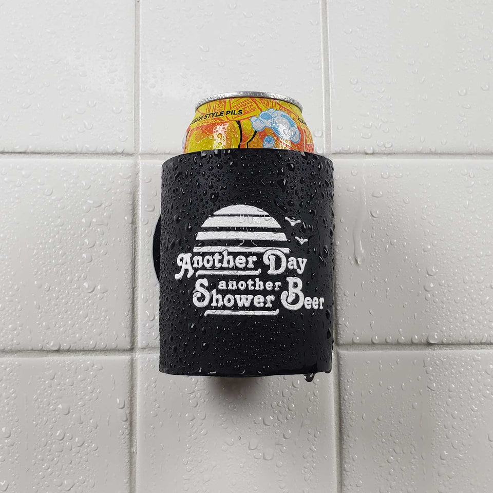 "Foam can beverage holder that sticks to shower wall via industrial velcro. This design is white ink printed on a black can holder with the words ""Another Day Another Shower Beer"" written and artwork depicting a California sunset and two seagulls flying. This is an action shot of the product sticking to a shower wall."