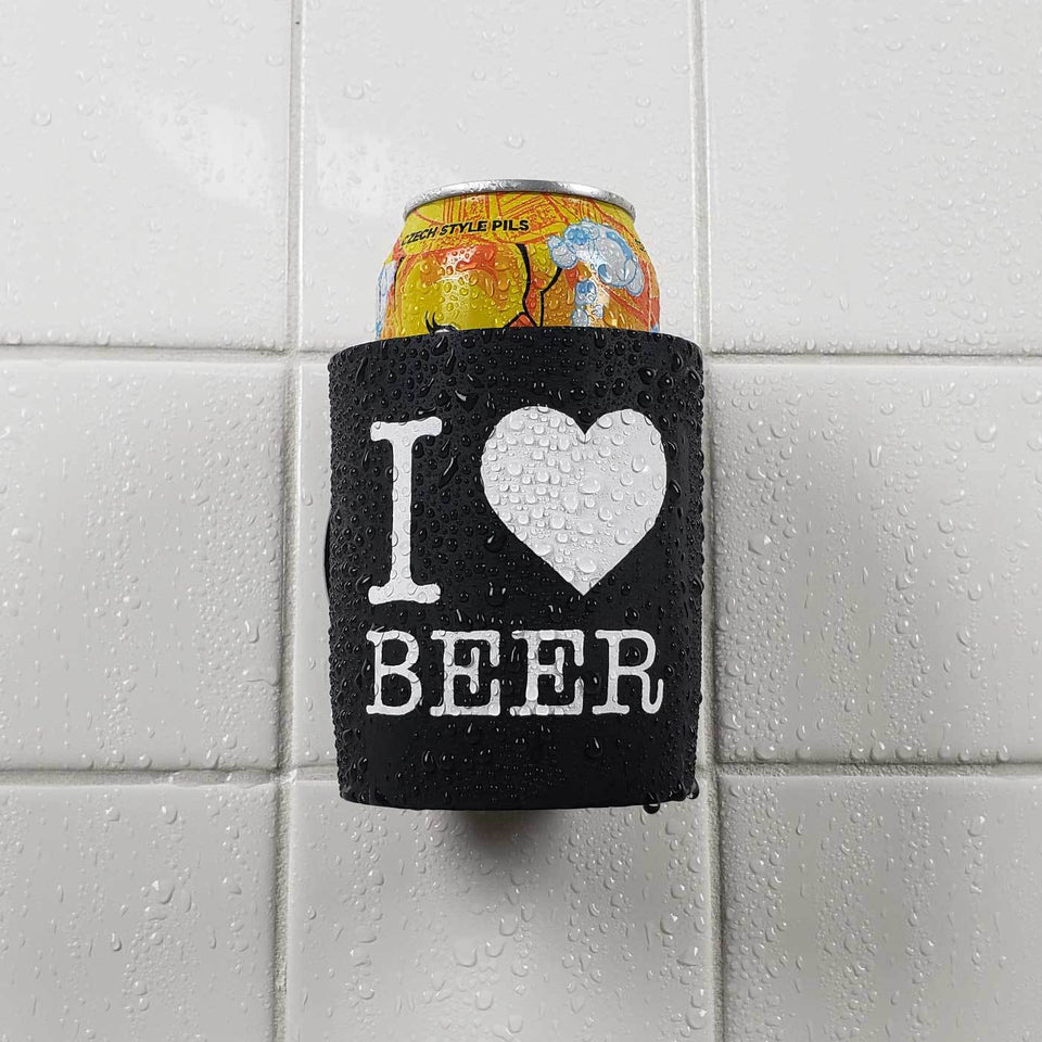 I Heart Beer design black foam can beverage holder with white ink sticking to a shower wall.