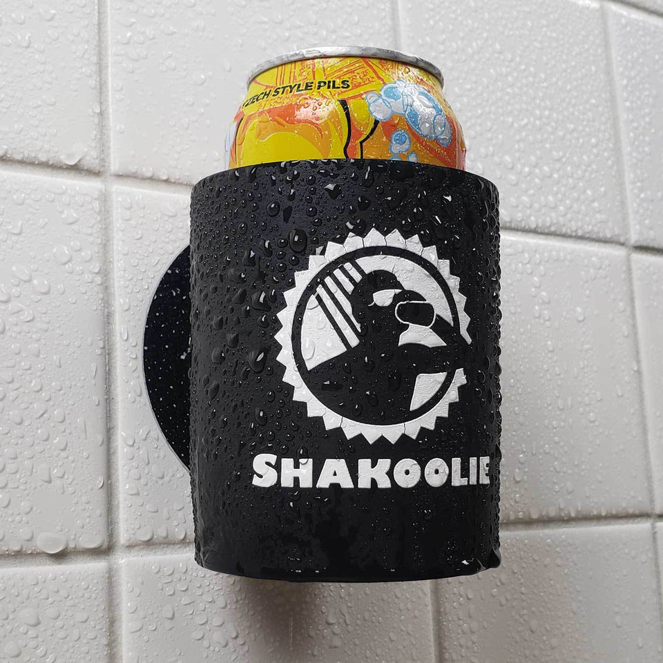 Shakoolie logo design black foam can beverage holder with white ink sticking to a shower wall.