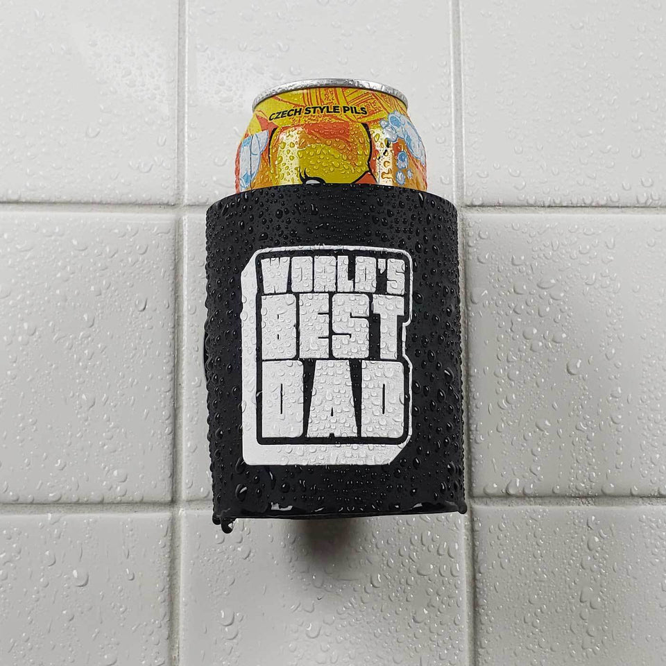 Worlds Best Dad design black foam can beverage holder with white ink sticking to a shower wall.
