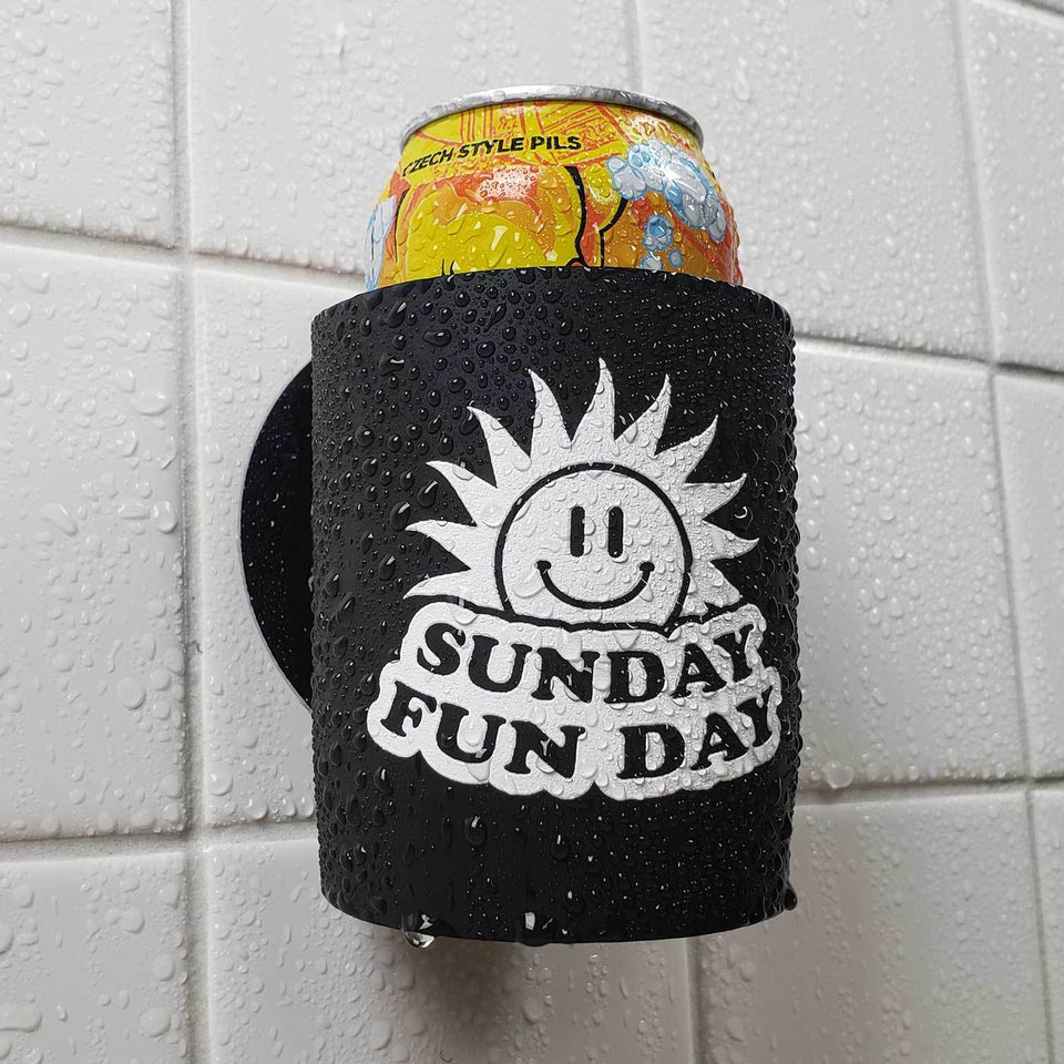 Sunday Funday design black foam can beverage holder with white ink sticking to a shower wall.