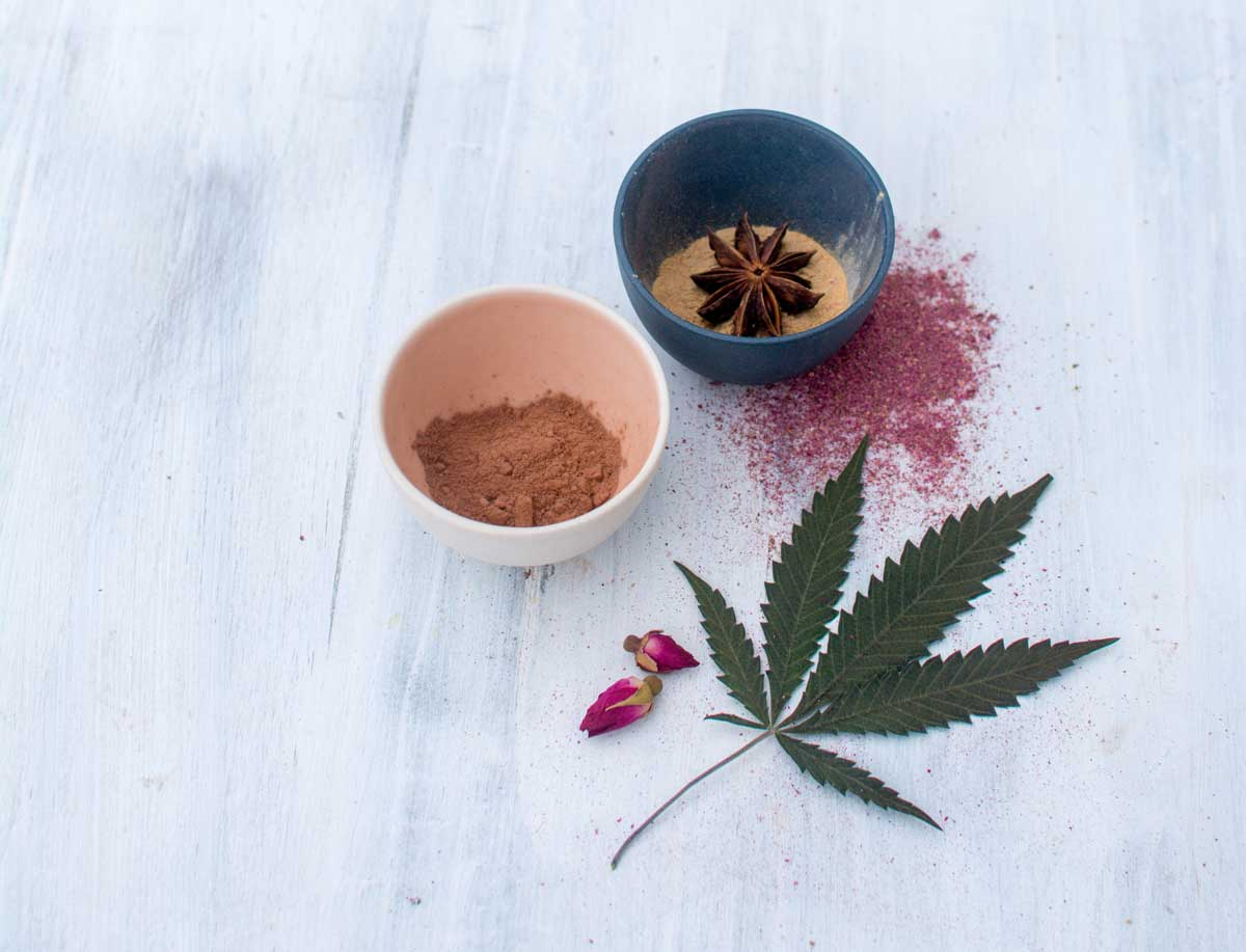 Cocoa powder, rose powder, maca and star anise in small bowls with cannabis leaf for sultry hot cocoa recipe