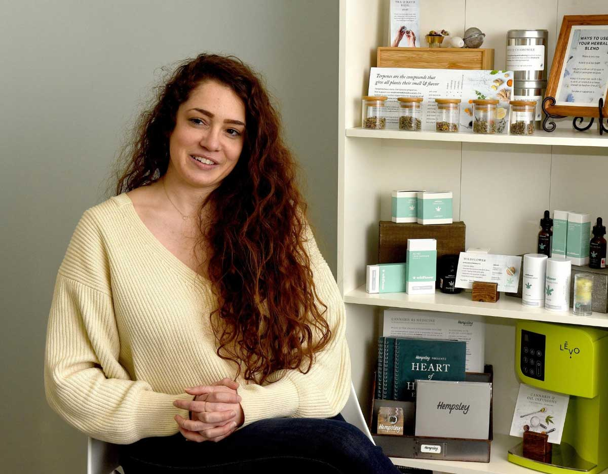 Kristen in Hempsley office next to shelf with CBD products and information