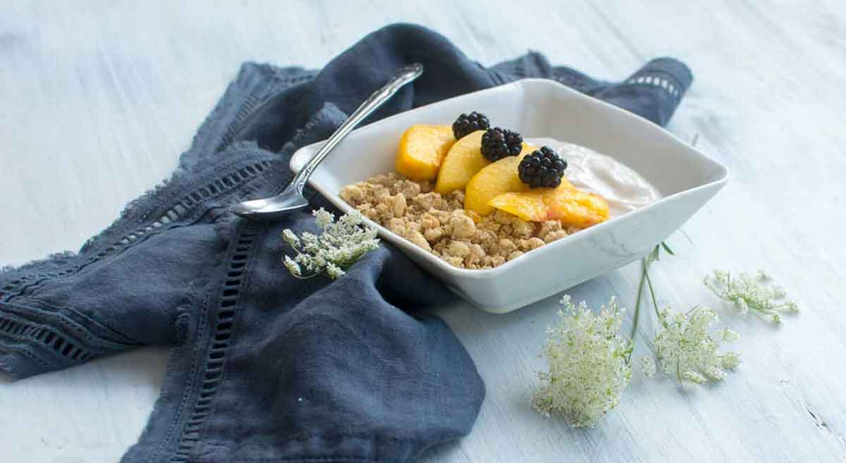 Simple CBD fruit dip with peaches, blackberries styled with vintage spoon and flowers