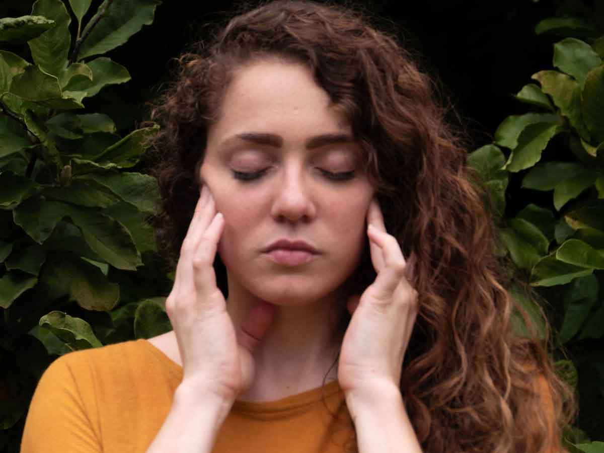 Woman massaging clenched jaw while stressed