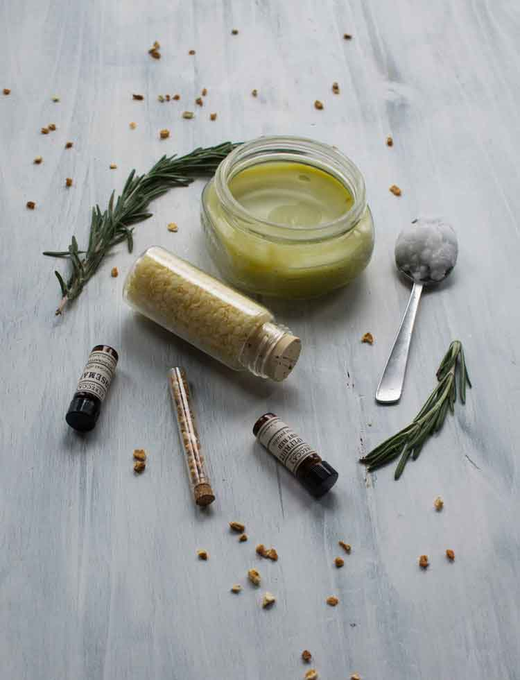 Styled ingredients of hemp oil body butter with beeswax, essential oils, coconut oil, and dried herbs
