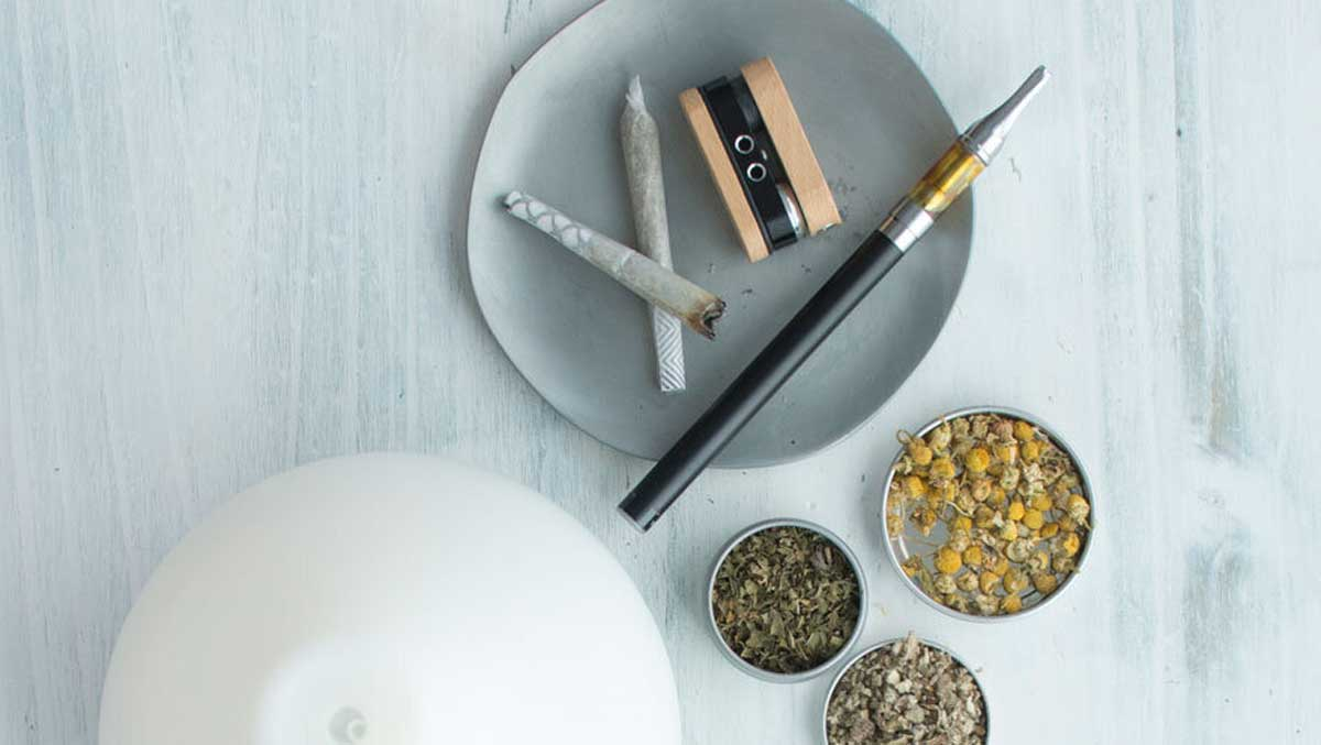 Dried herbs with the vaporization tools vape pen, pipe, joint, and essential oil diffuser