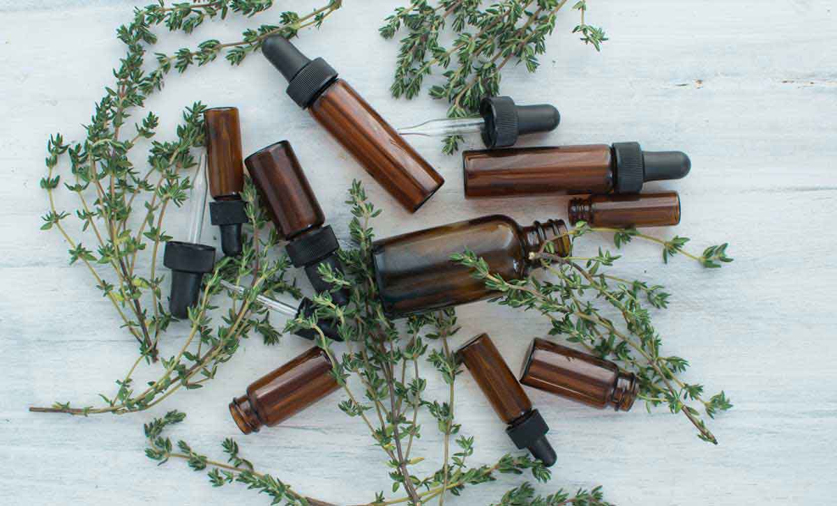 Tincture bottles with fresh thyme for making your own tinctures at home