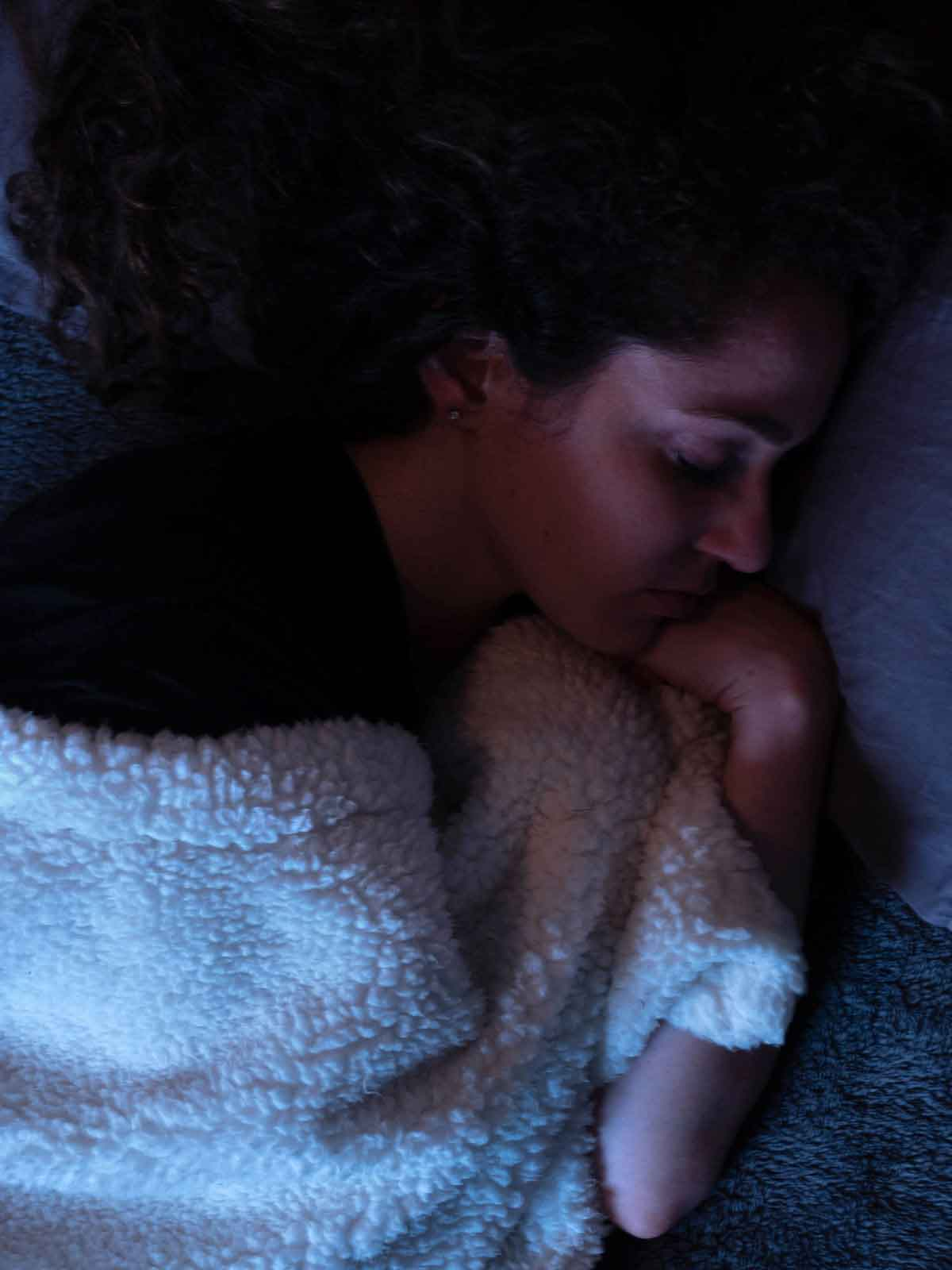 Woman sleeping with cozy white blanket to support her endocannabinoid system