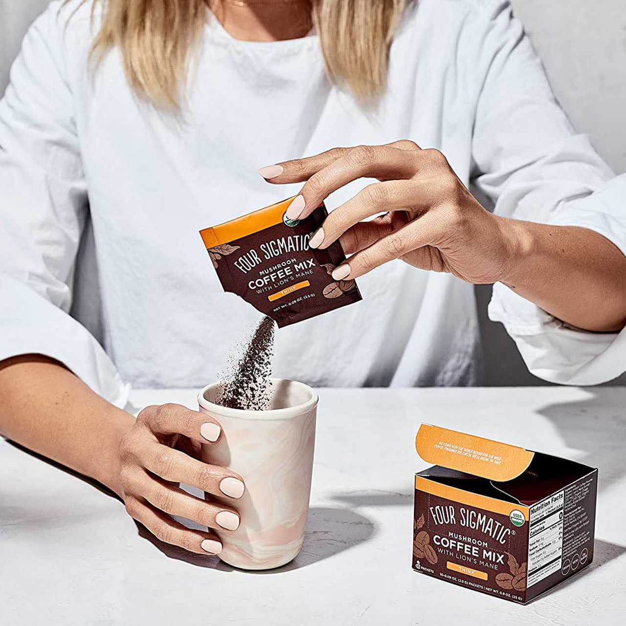 Woman pouring Four Sigmatic instant coffee packet in her cup.