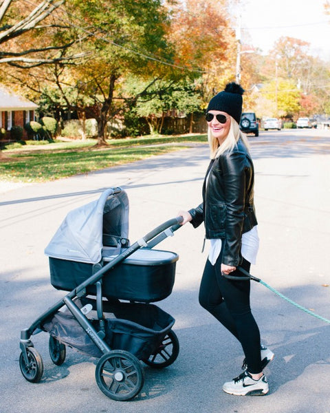 Stylish mom pushing stroller