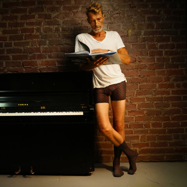 Rudy in RLTD mens underwear and socks standing next to a piano.