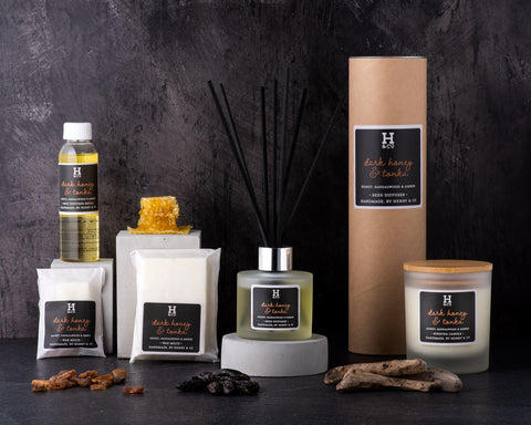 Henry & Co home fragrance Dark honey & tonka Collection, wax melts, reed diffusers, scented candles, reed diffuser refills surrounded by honey comb