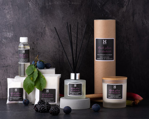 Henry and co home fragrance black plum and rhubarb fragrance collection, reed diffuser, scented candle, reed diffuser refill and wax melts surrounded by fresh fruit