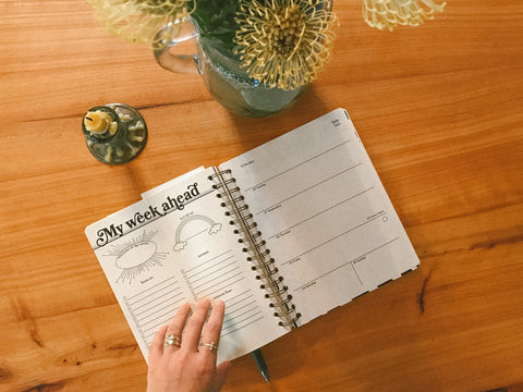 A hand opens a weekly planner over a wooden table next to a vase of yellow flowers and an unlit beeswax taper candle.