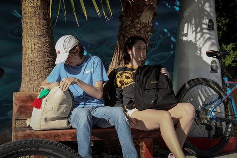 A young man and a young woman are sitting on a wood bench in front of palm trees and holding their backpacks on their lap