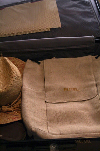 The beige backpack is set flat inside a suitcase, next to a straw hat